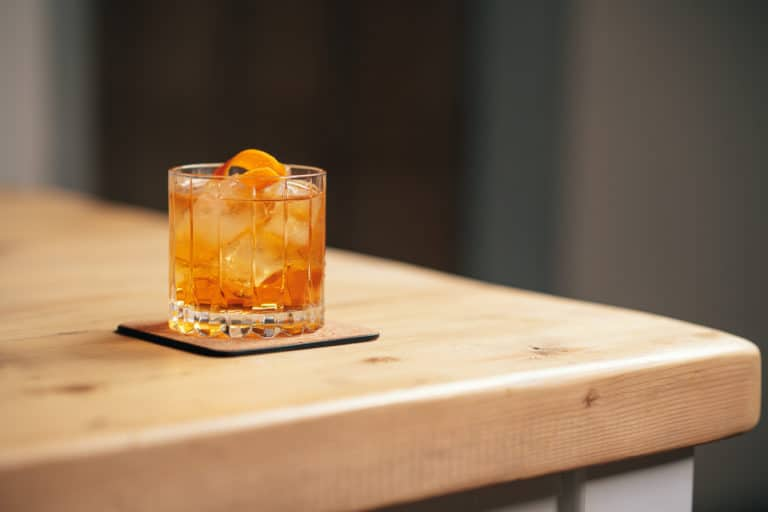 Old Fashioned Cocktail in a rocks glass with orange slice garnish on a wooden table