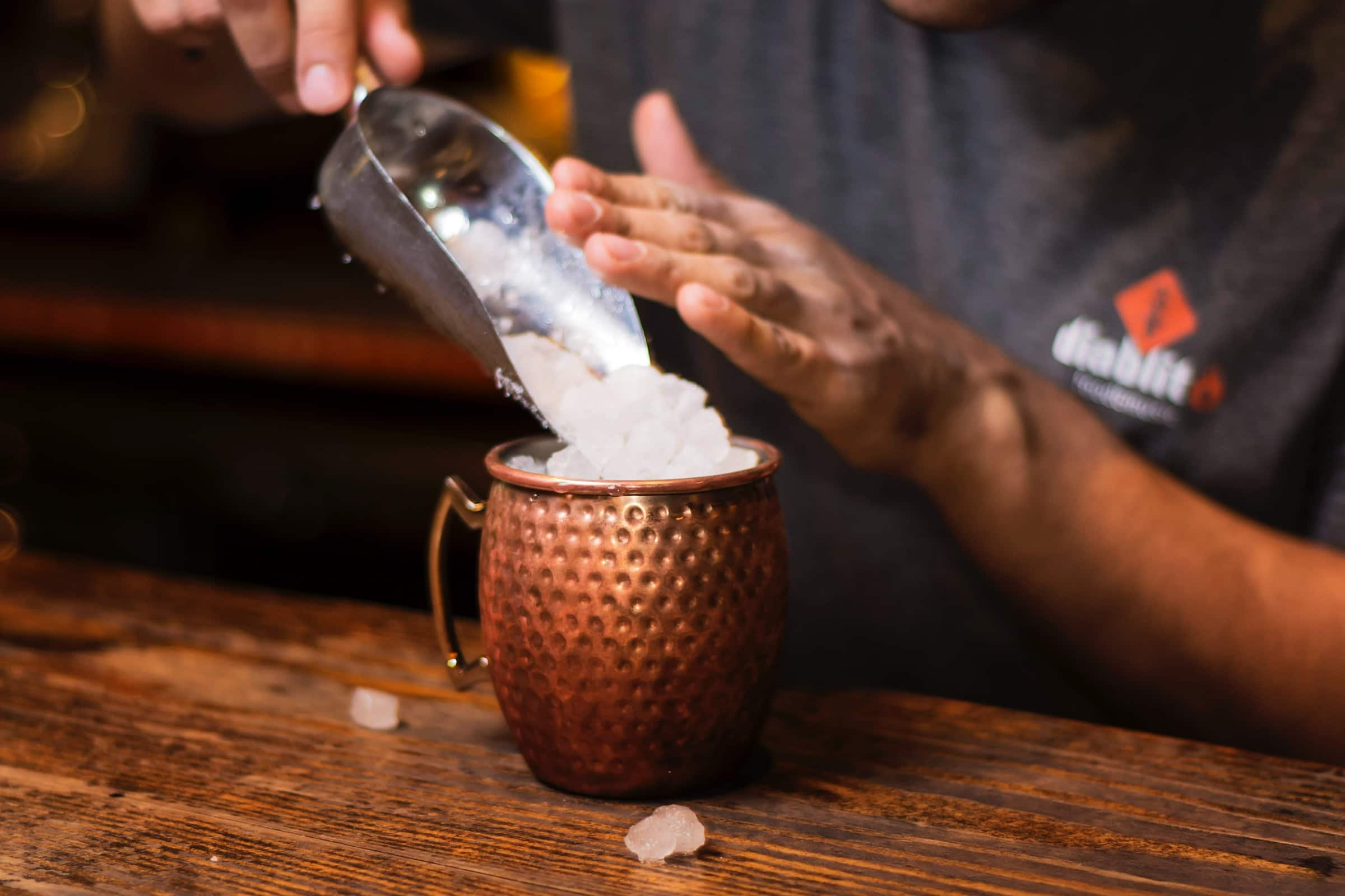 A bartender pours ice into a copper cocktail mug showing how to blend cocktails with ice
