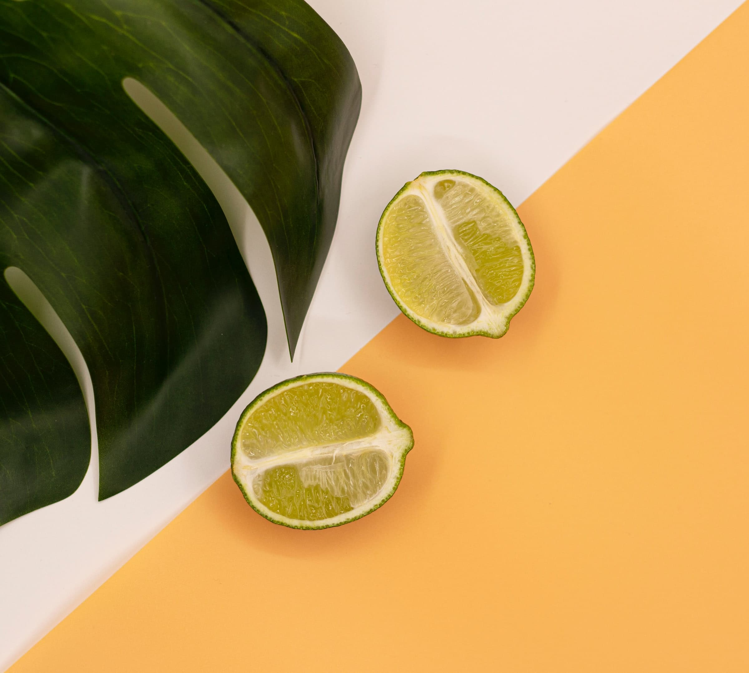 Two half limes cut in half by a green leaf on an orange and white background