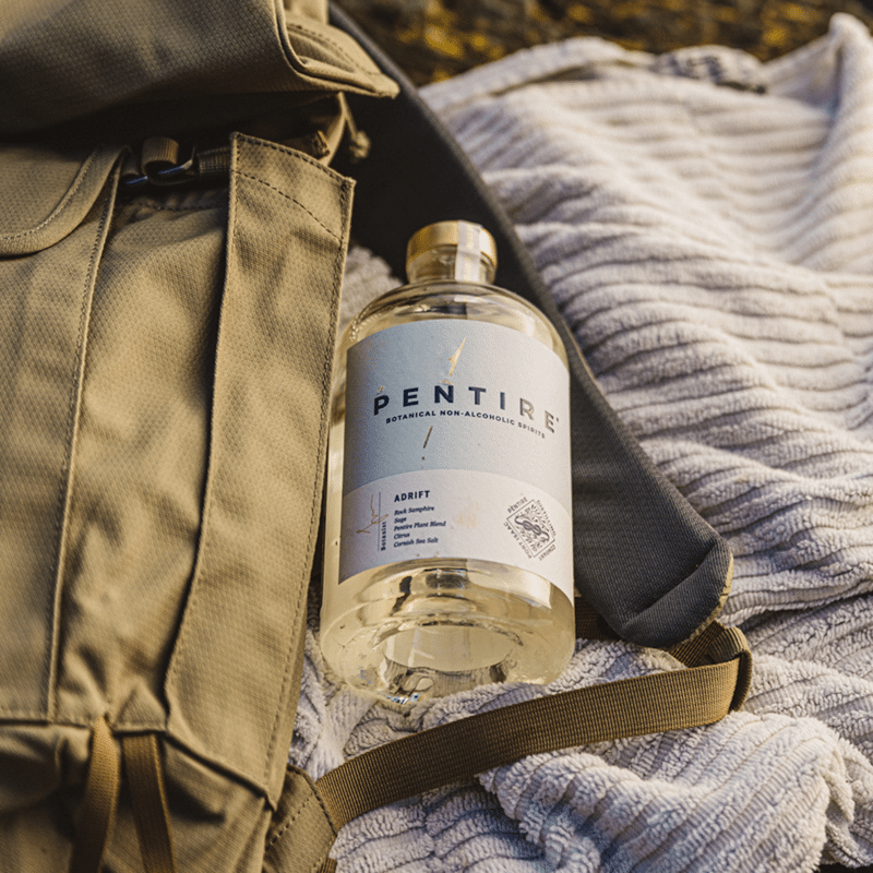 A bottle of Pentire Adrift low alcoholic gin lies on top of a satchel and rug in the late evening sunlight