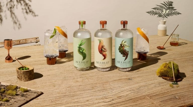 Bottles of Seedlip Non Alcoholic Gin - Seedlip Grove 42, Seedlip Garden 108 and Seedlip Spice 94 sit on a wooden table by a glass of gin and tonic with an orange peel twist garnish.