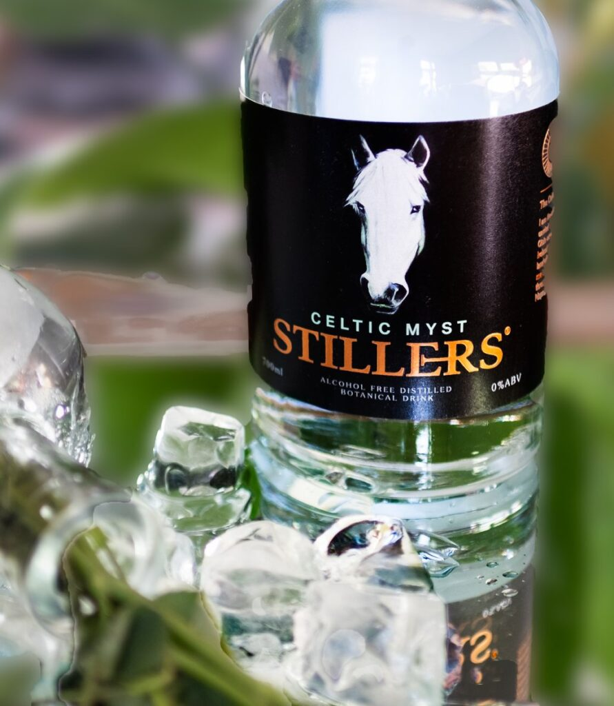 A bottle of Stillers Celtic Myst Non Alcoholic Gin sits on a green leaf alongside several ice cubes