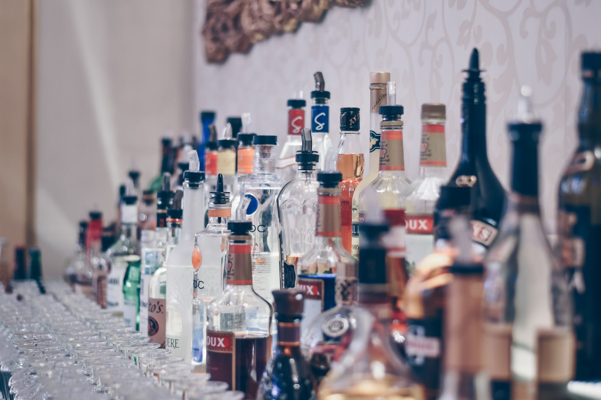 Bottles of alcohol stacked in rows on the back of a bar by a wall. Image by ibrahim-boran on Unsplash.
