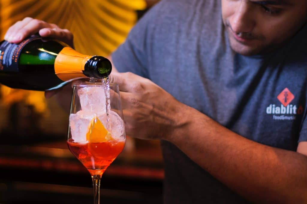 A male bartender shows how to build a cocktail by pouring sparkling wine into a wine glass filled with ice and an orange liqueur. Photo by Kike Salazar N on Unsplash