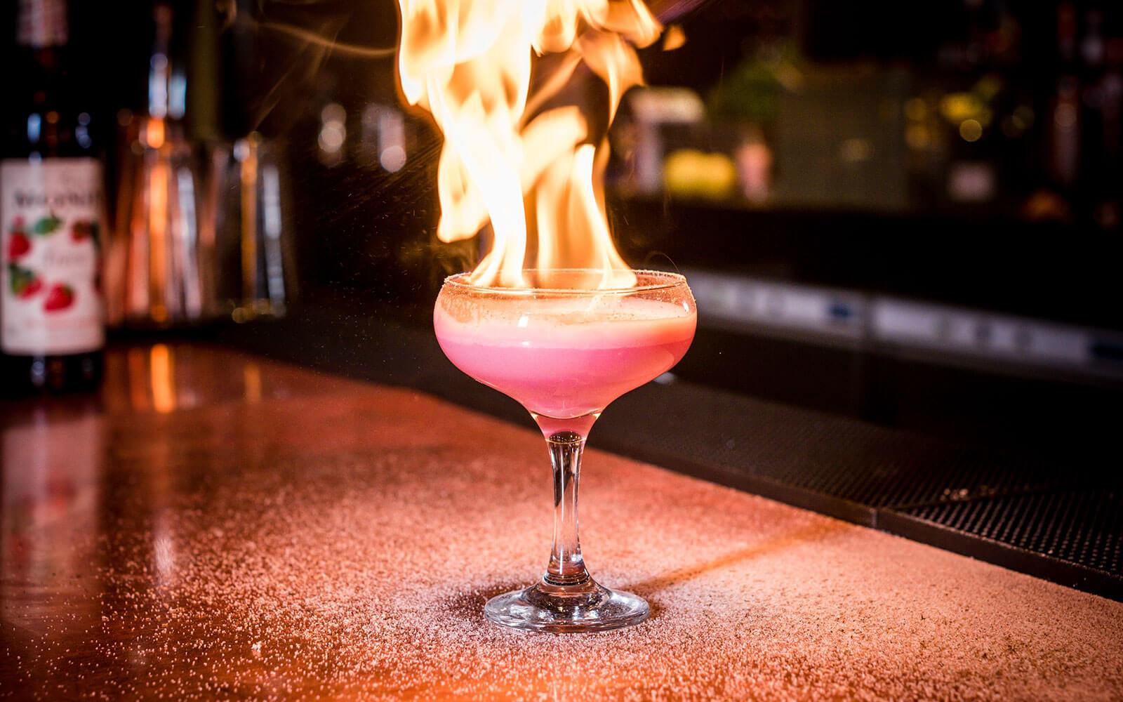 A cocktail with a flaming top at Aluna, one of the best bars in Birmingham