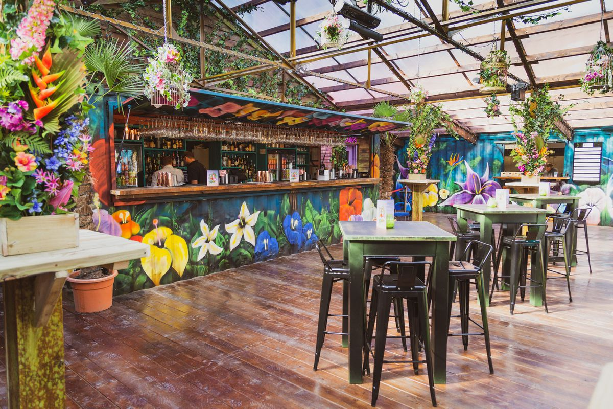 Bars and tables set up by the floral, Hawaiian beach bar inspired Birdies Bar and Barbeque Digbeth