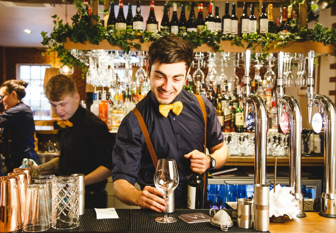 A bartender in braces and bow tie sets up a wine glass on the bar of Saint Pauls House