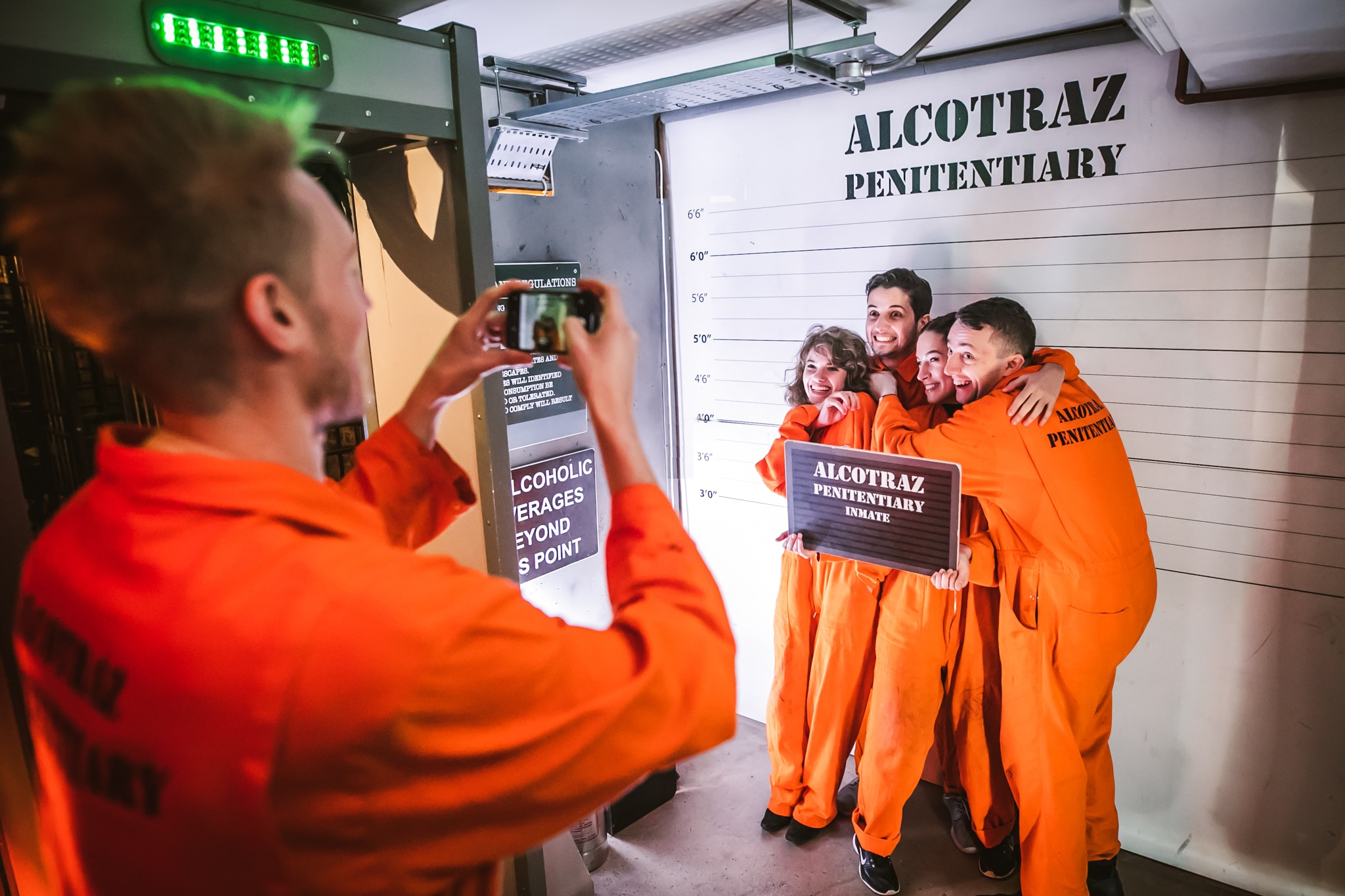 Four people in orange prison jumpsuit costumes post in front of a Alcotraz bar London sign designed like the police line up parades.