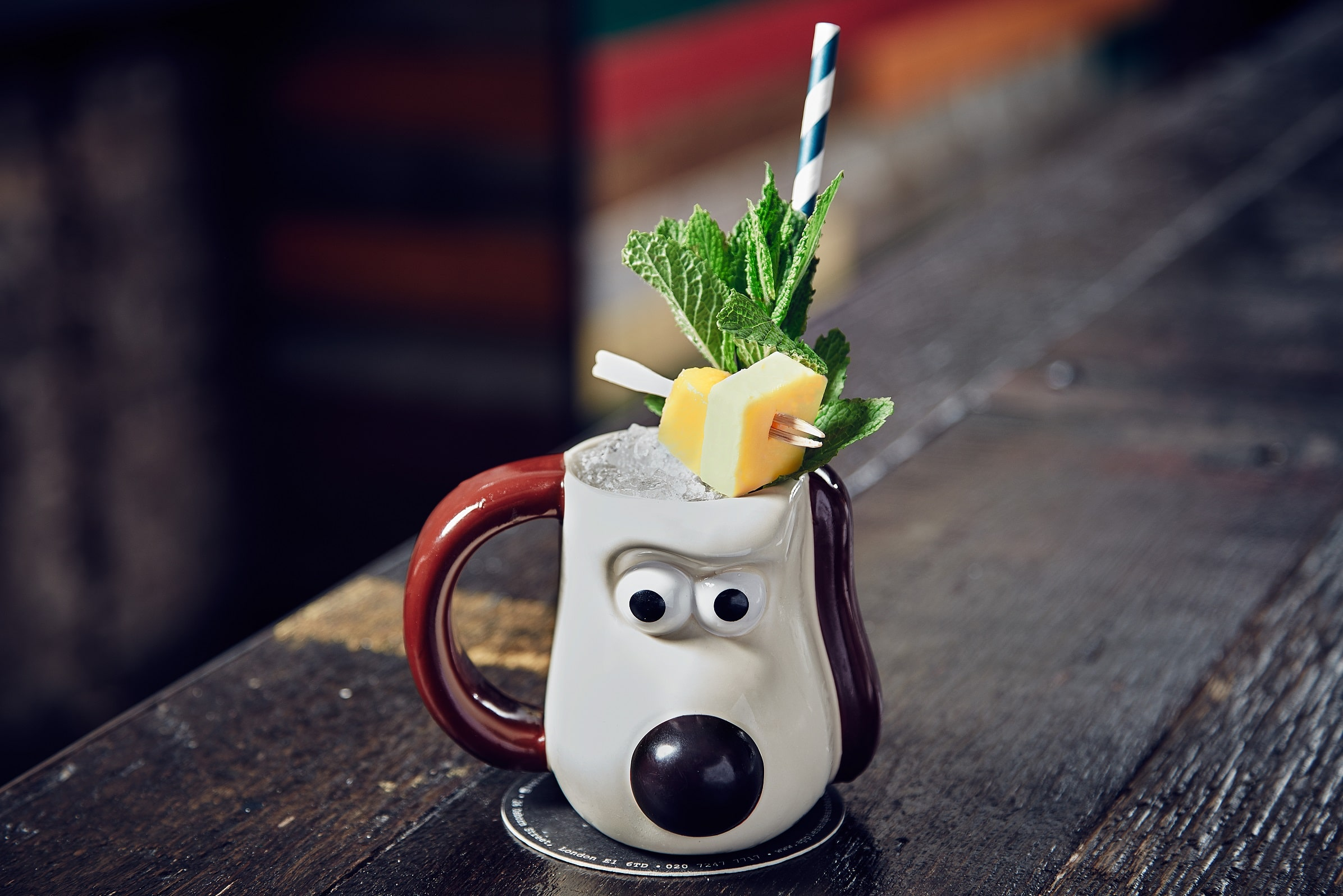 A Gromit mug containing a cocktail with a cheese garnish at Apples and Pears, one the best bars in London