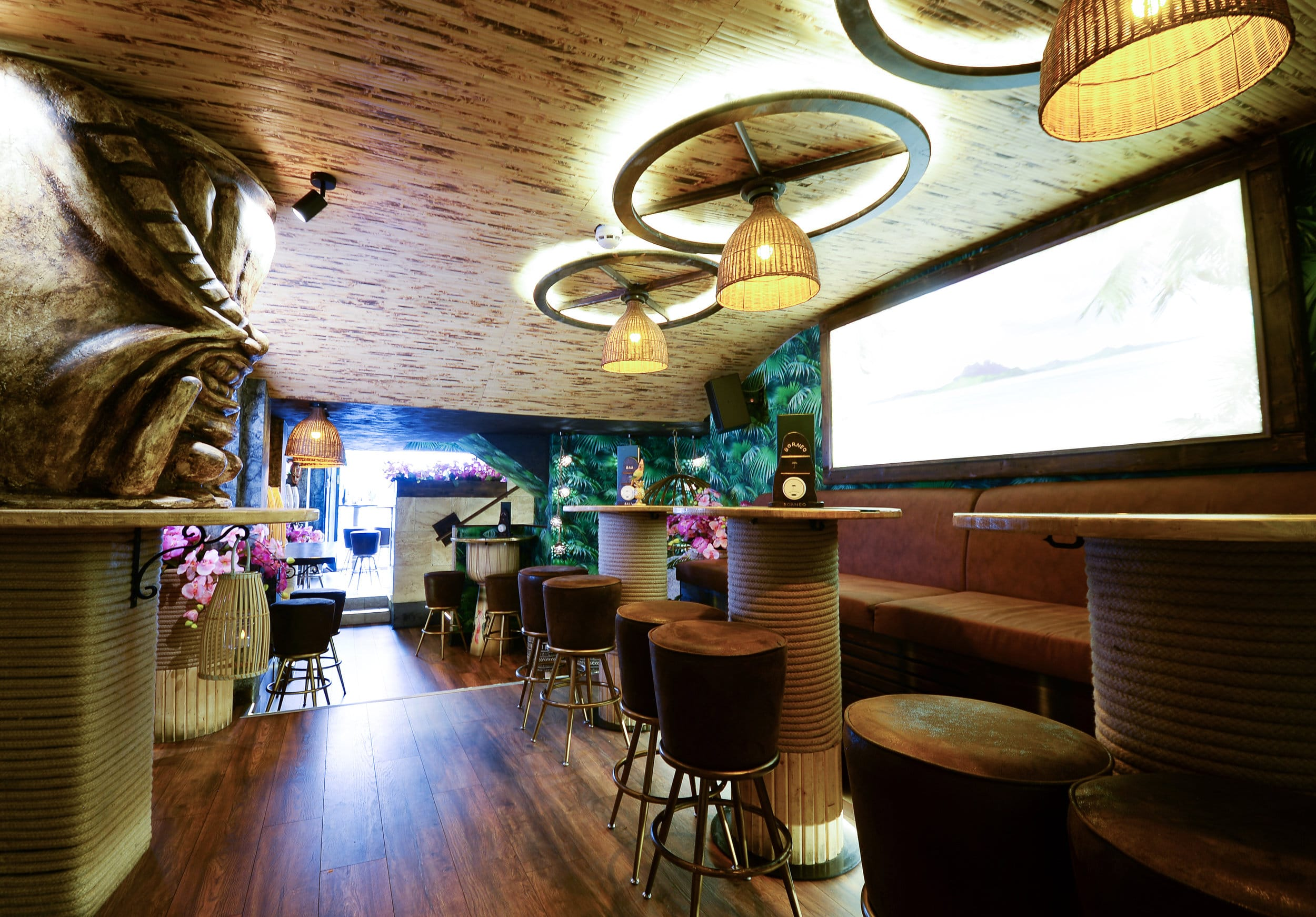 The inside of Laki Kane bar London - and underground tiki inspired cavern space with wooden carvings for pillars, hessian rope wrapped around the table stems and green palm tree fronds painted on the walls