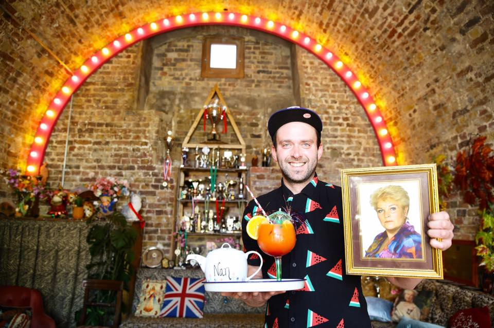 A man in a shirt with a pattern of melon slices and cap holds a picture of Pat Butcher from Eastenders in one hand, and a tray with a teapot and cocktail in the other, at Little Nan's bar Deptford, London
