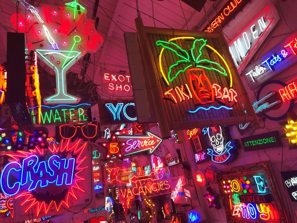 A collection of neon signs hang from the ceiling at God's Own Junkyard bar in London