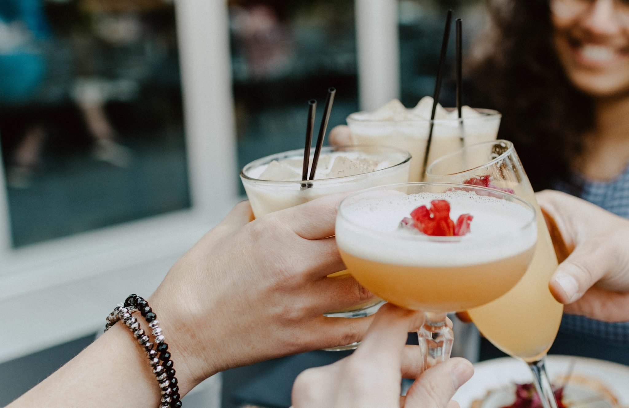 People holding cocktails - french martini and long island iced tea, saying cheers. The best summer cocktails -Photo by Kelly Sikkema on Unsplash