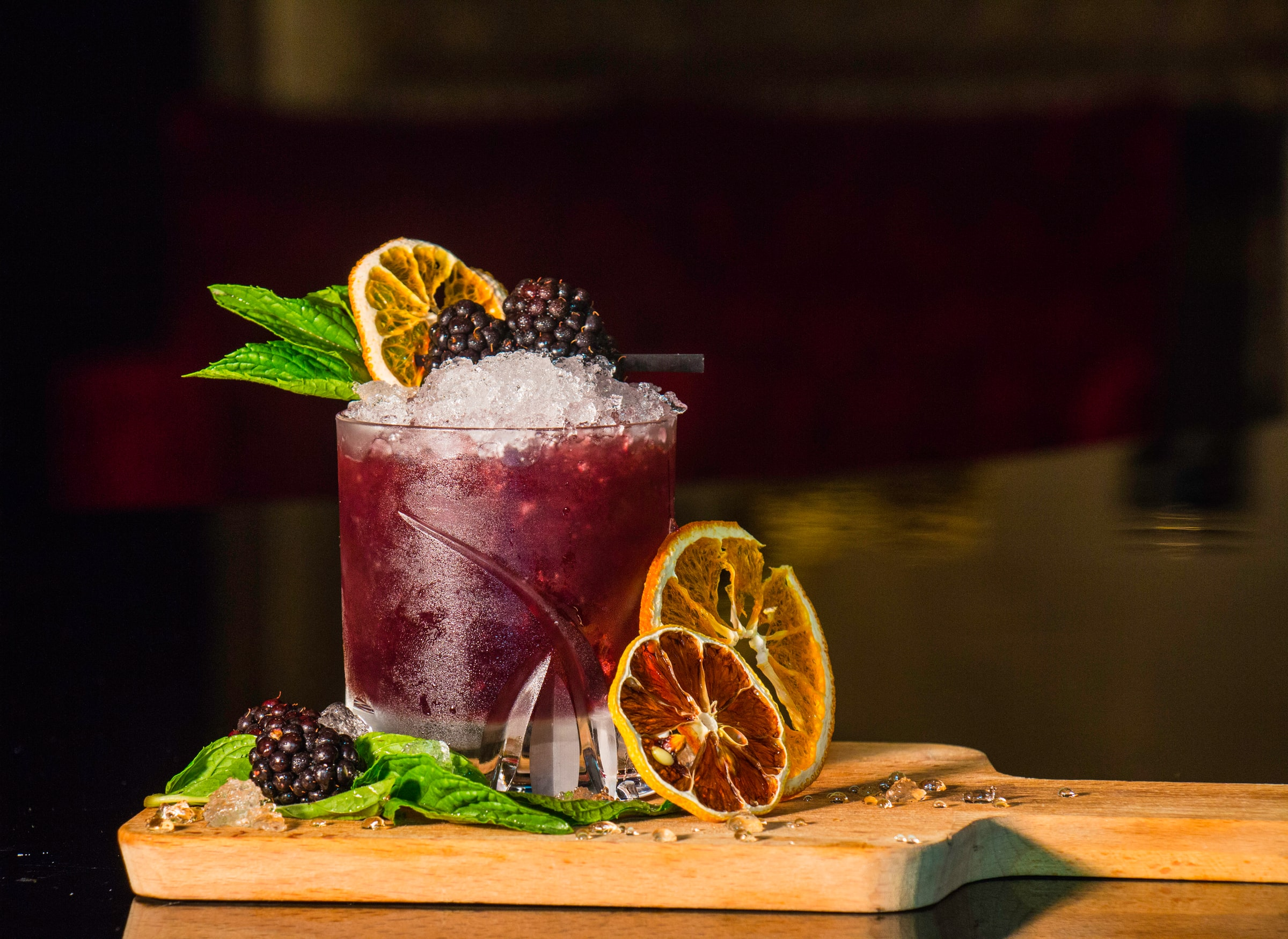 A bramble cocktail sits on a wooden board with blackberries, basil leaves and dehydrated orange slices as decoration and garnish - Photo by Proriat Hospitality on Unsplash