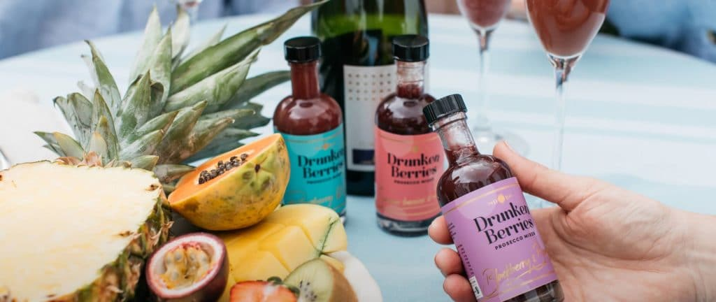 Three bottles of prosecco mixers alongside passionfruit, mango and other fruits