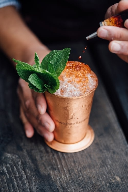 A bartender drips cocktail bitters into a cocktail in a copper mug, with a mint sprig garnish