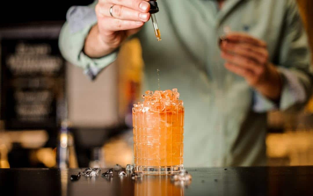 A bartender drips cocktail bitters into a cocktail in a rocks glass