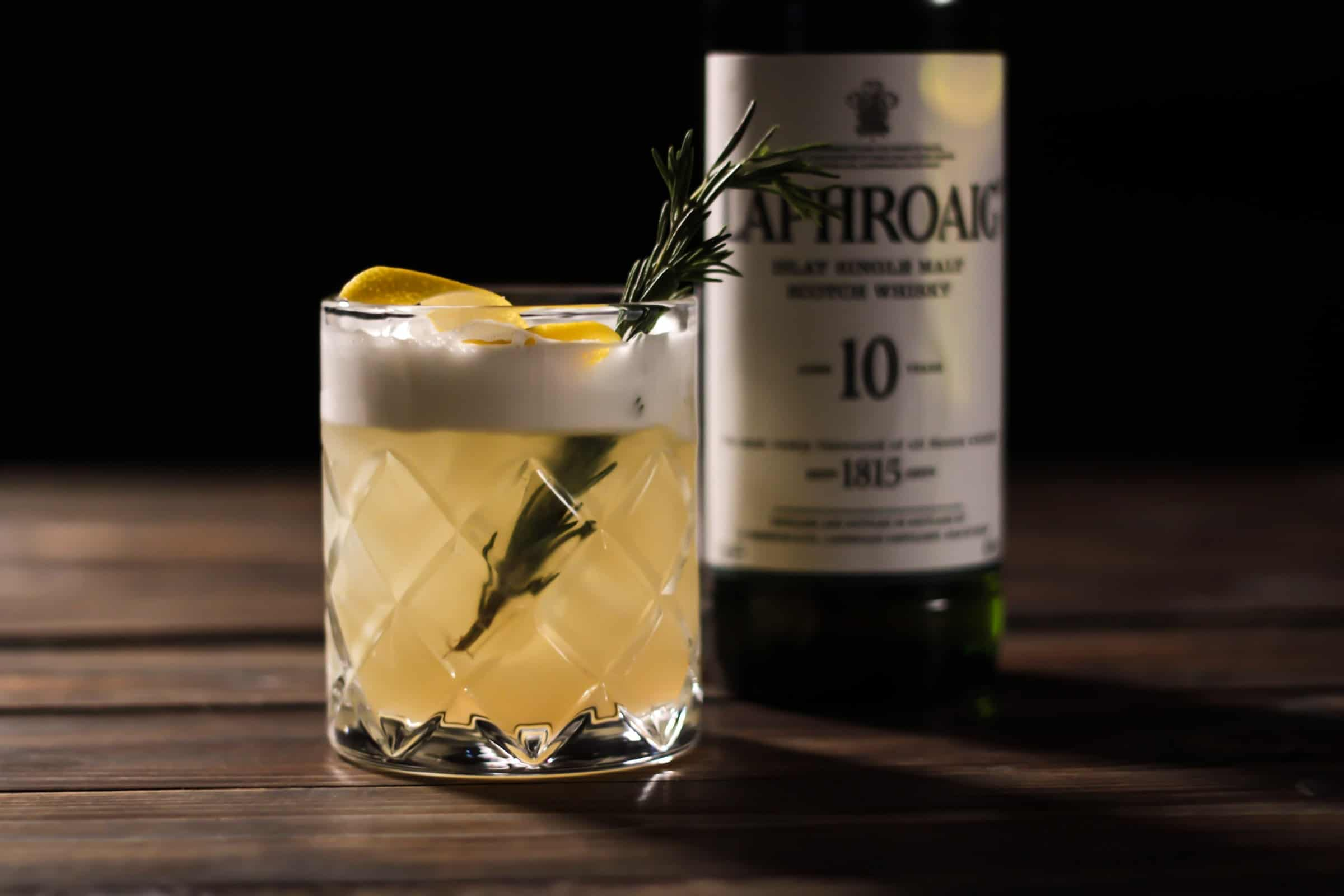 A whisky sour cocktail in front of a bottle of Laphroaig Whisky