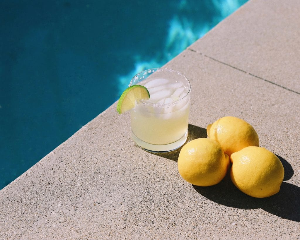 A margarita in a rocks glass sits by three lemons by the edge of a pool. Photo by Taylor Simpson on Unsplash