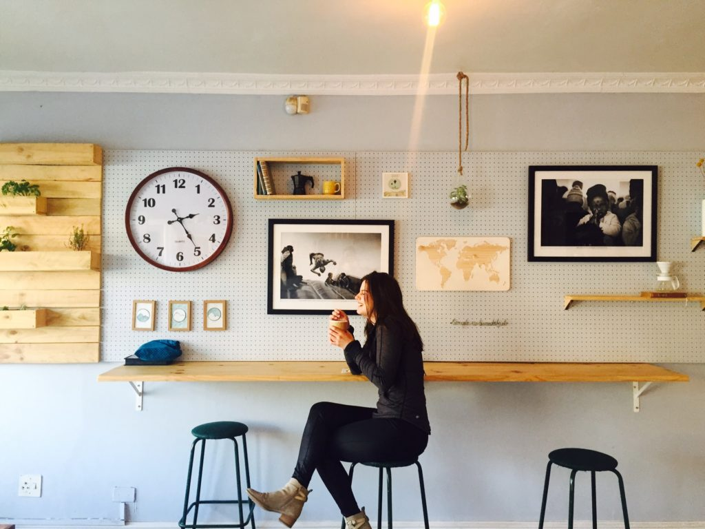 A woman sits sipping a drink in a trendy home bar