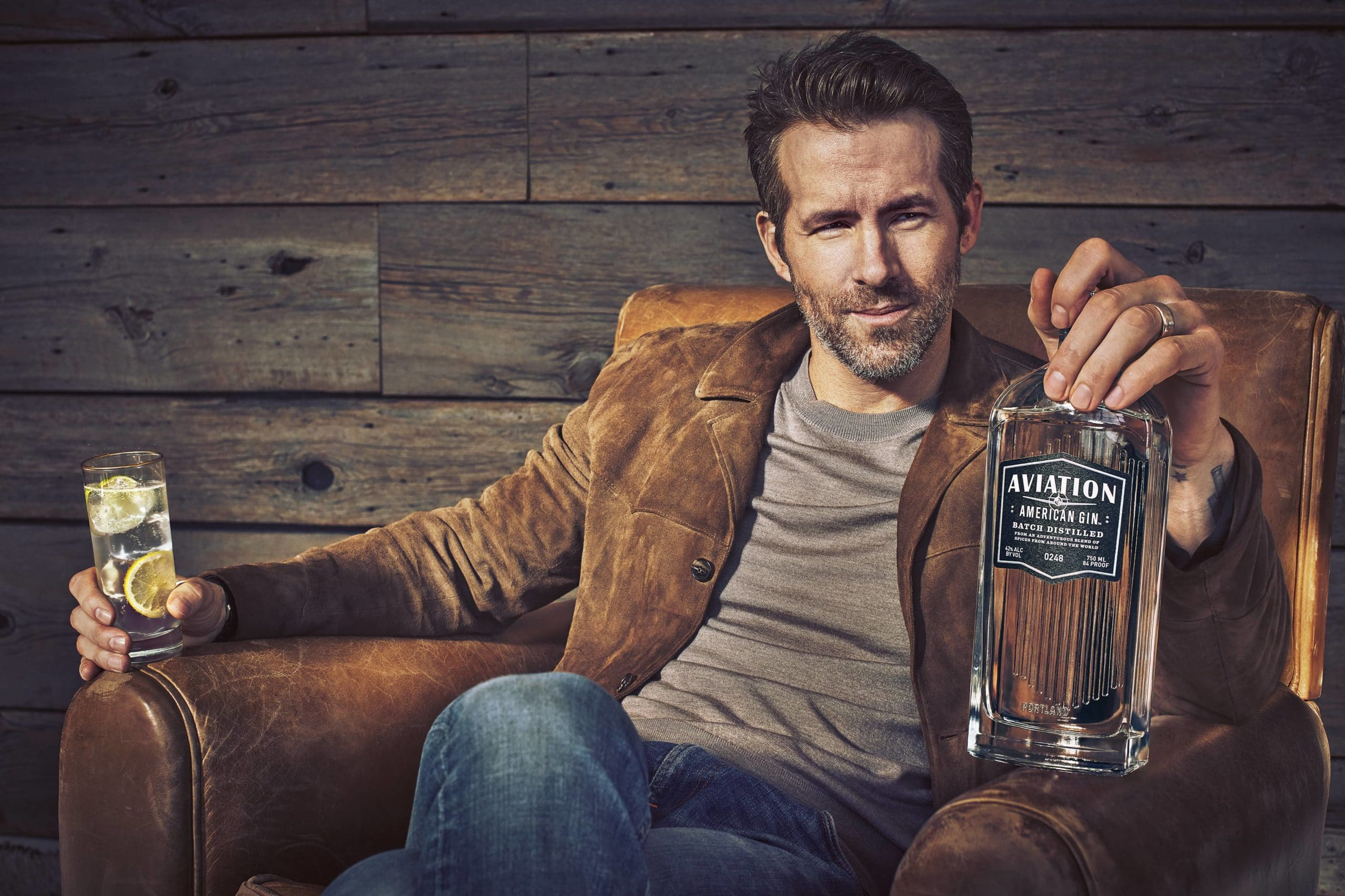 Ryan Reynolds holding a bottle of Aviation Gin, named after the Aviation Cocktail Recipe