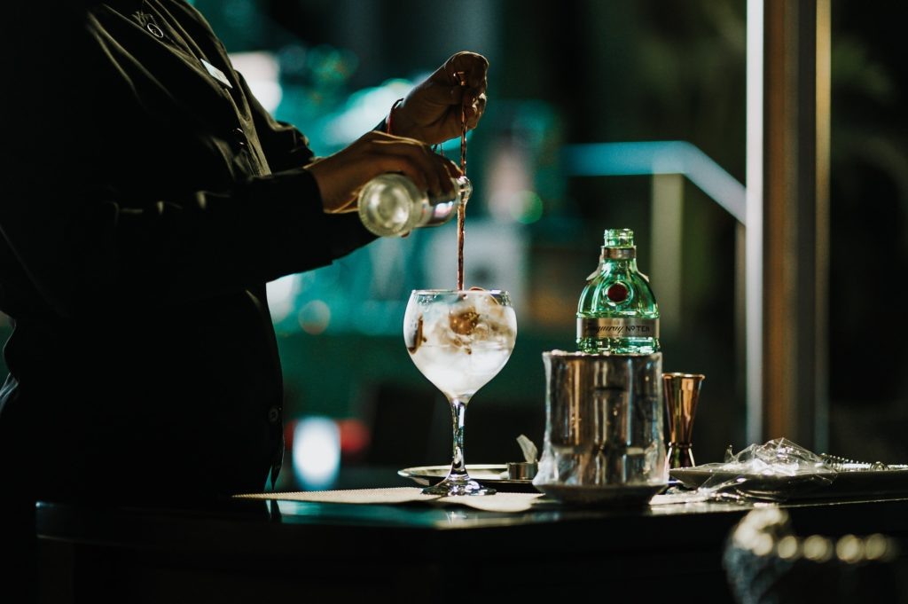 A bartender in shadow pours cocktail mix into a glass