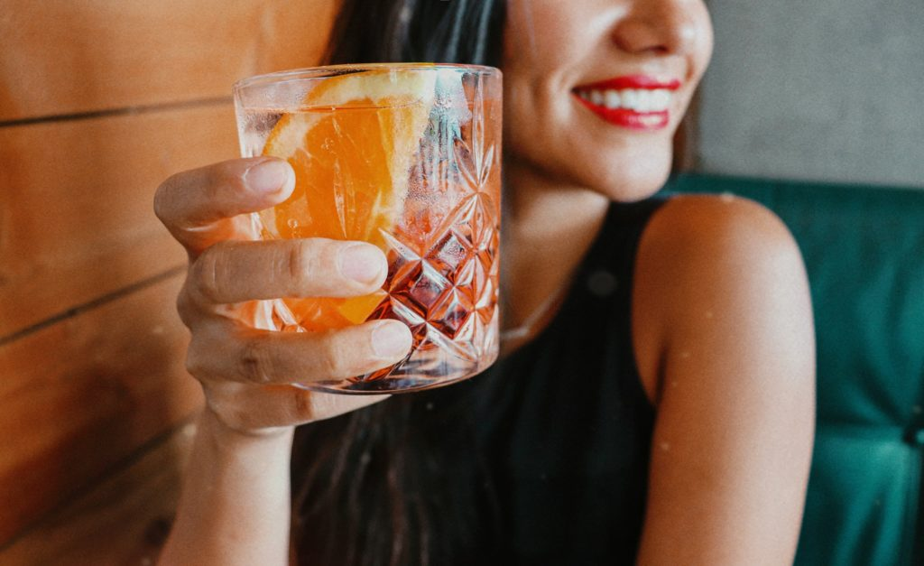 A woman holds a negroni sbagliato