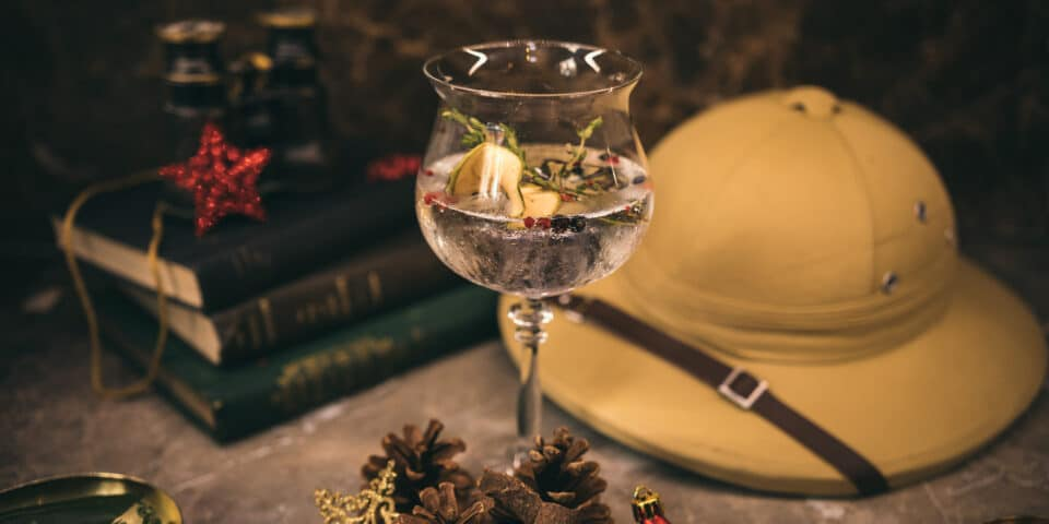 A gin in a Balon glass next to a pith helmet and other Victorian themed decorations, from Mr. Fogg's Gin Safari