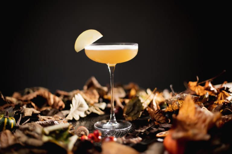 A Toffee Apple Martini created by The Cocktail Society in a bed of Autumn leaves